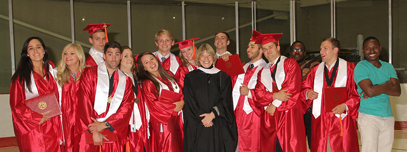 Group picture of cohort 1 in graduation caps and gowns at Goggin
