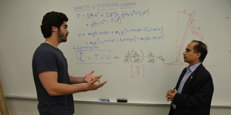 Dr. Shukla and graduate students working on an equation on classroom white board