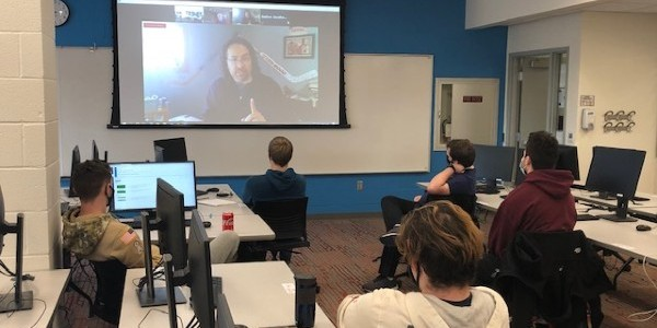A group of students facing a Zoom session projected on a screen