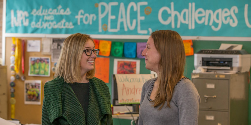 two people talking in a classroom with a peace poster in the background