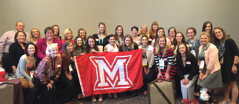 group of nutrition students taking a photo with the Miami flag