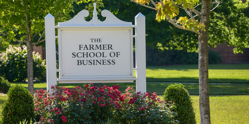 White Farmer School of Business sign in flowerbed
