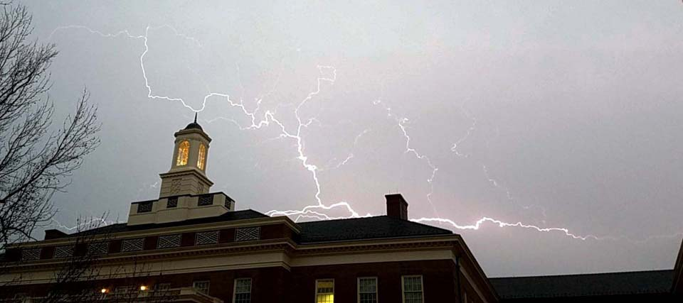 Lightning crackles over the top of the Farmer School