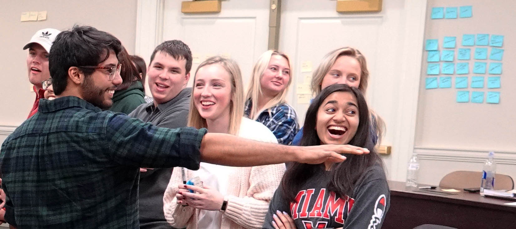 Male student pointing as female students laugh