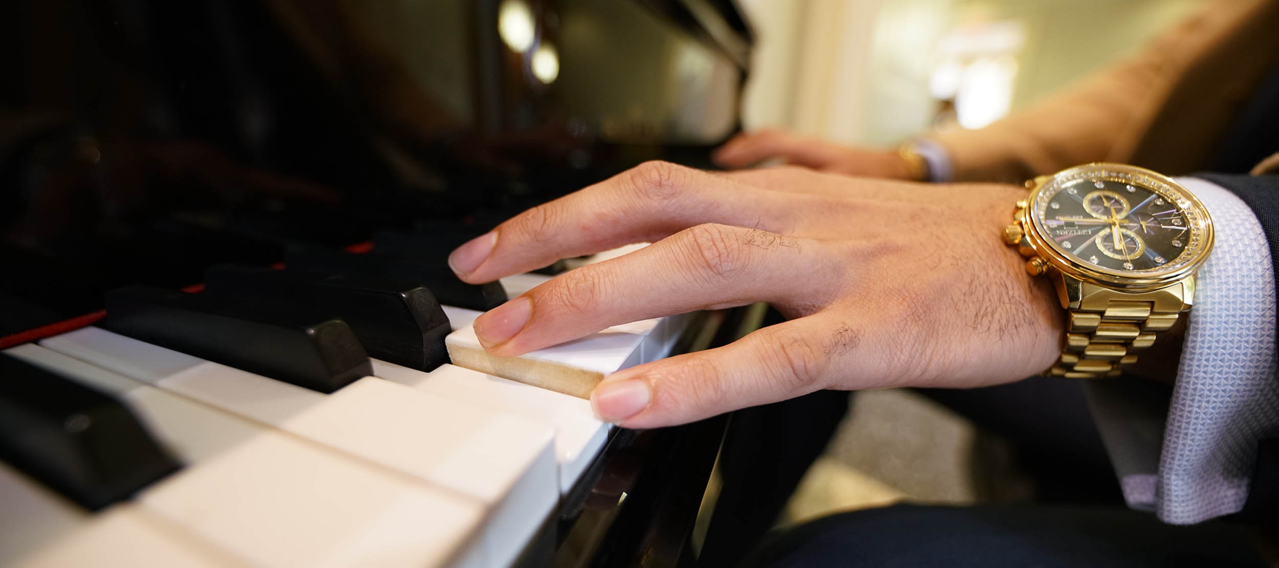 A closeup of a hand playing the piano in the Forsythe Commons