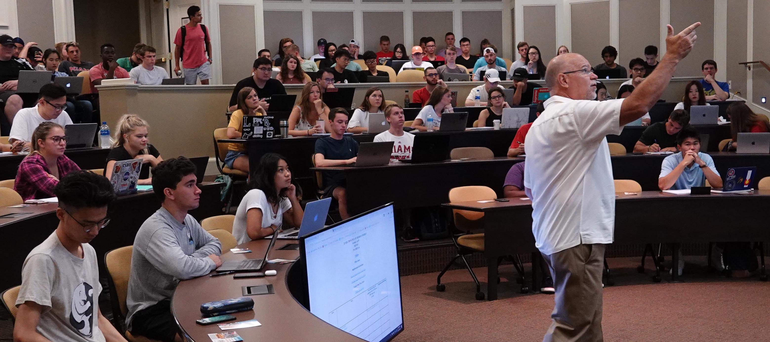 Instructor gestures toward the screen during the first day of classes