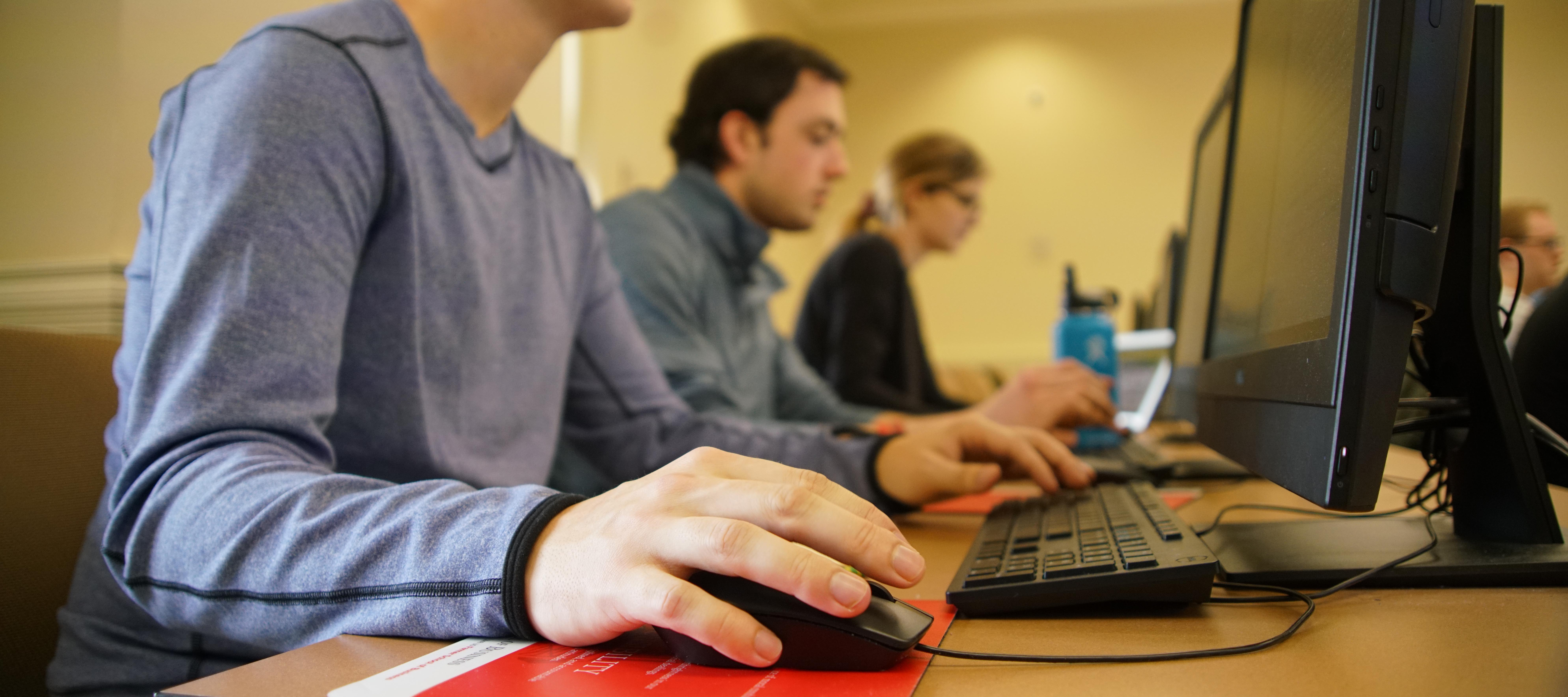 Hand and mouse in focus, people blurred behind it in classroom