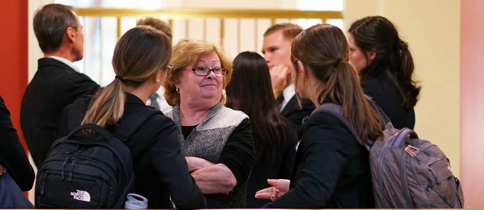 Students surround Jan Taylor after their first round in the West Monroe Partners case competition