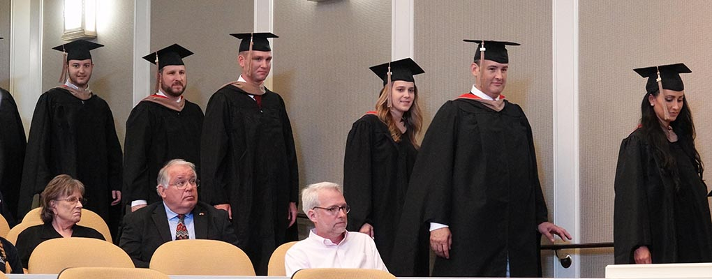MBA graduates line up at graduation