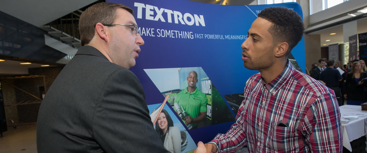 textron recruiter shaking hands with interested student at career fair