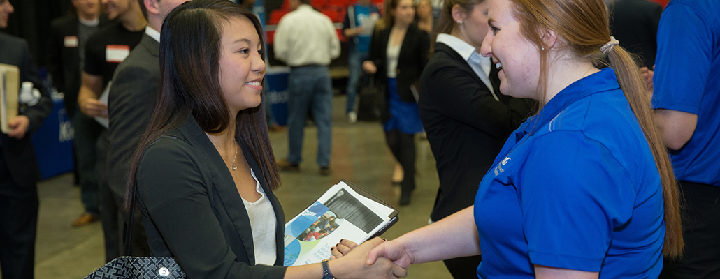 A young woman shakes hands with an employer at Career Fair