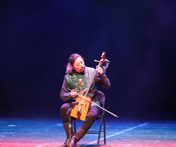 A man sits along on stage playing a string instrument that he holds in his lap
