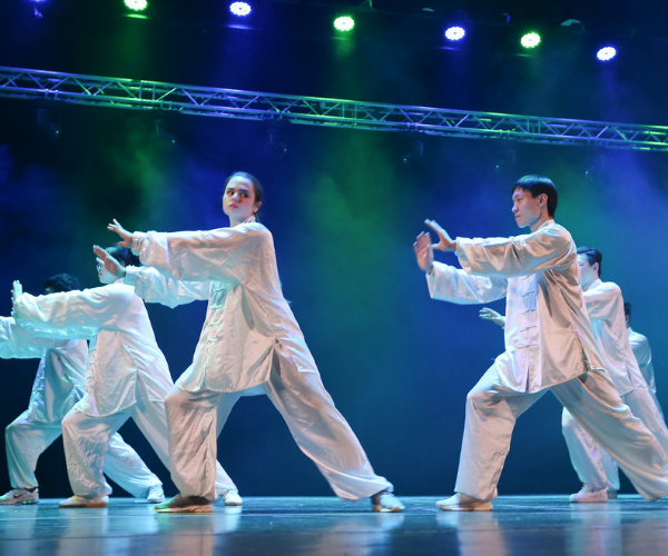 a group of people in white outfits perform tai chi. They stand on stage looking to the left, with their arms stretched out in front of them