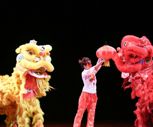 people in Chinese lion costumes stand on either side of a girl in the middle, who shakes one of the lions' hands