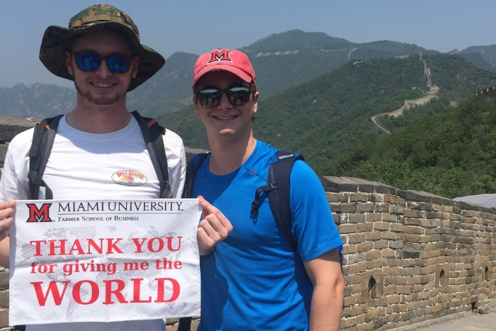 "Miami Students in front of the great wall of China holding a sign that says ""Thank you for giving us the world"" with a Farmer School of Business logo on it"