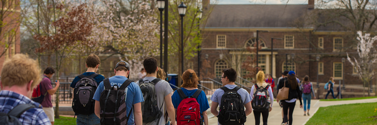 Students near Armstrong Center walk toward MacMillan Hall