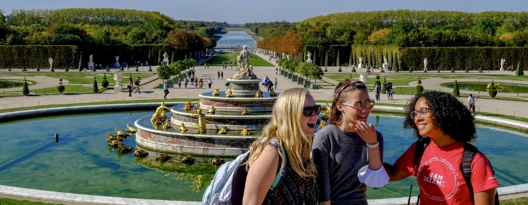 3  student laughing abroad in Paris in front of a fountain outside of Versailles