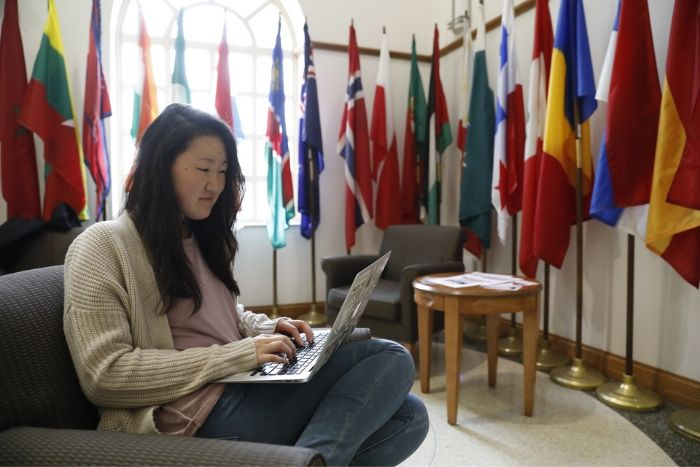student sitting in MacMillan Hall working on laptop, flags from many countries in background