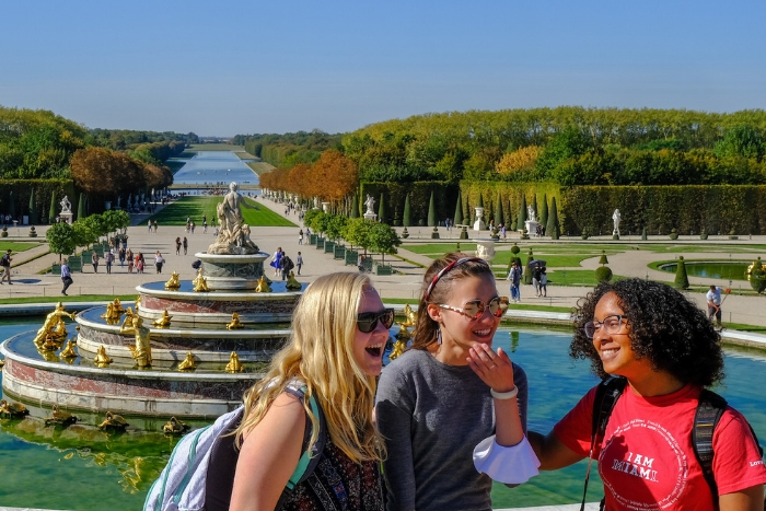 three study abroad students in Paris at Versailles gardens, smiles, laughing, wearing Miami shirt