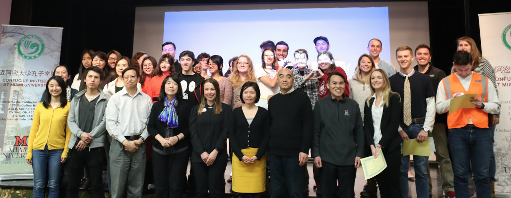 CIMU staff and students posing in front of the stage.