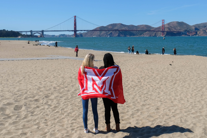 two students holding Miami flag behind them as they stand on a beach in San Francisco