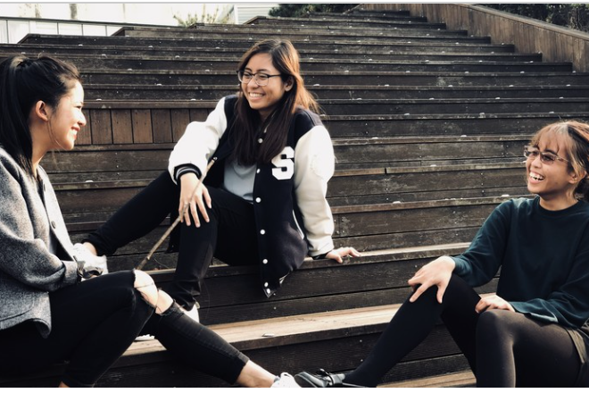 Smiling students recline on steps