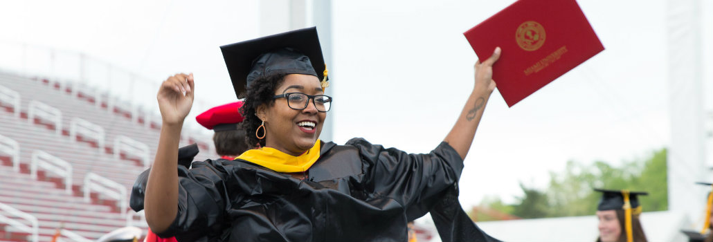 Student excited after receiving their diploma at commencement