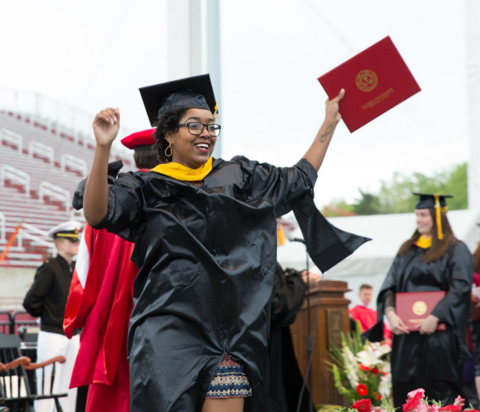 A Master's student celebrating after being given their diploma