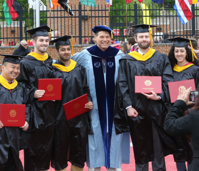 Group of Master's students with a professor at May Commencement