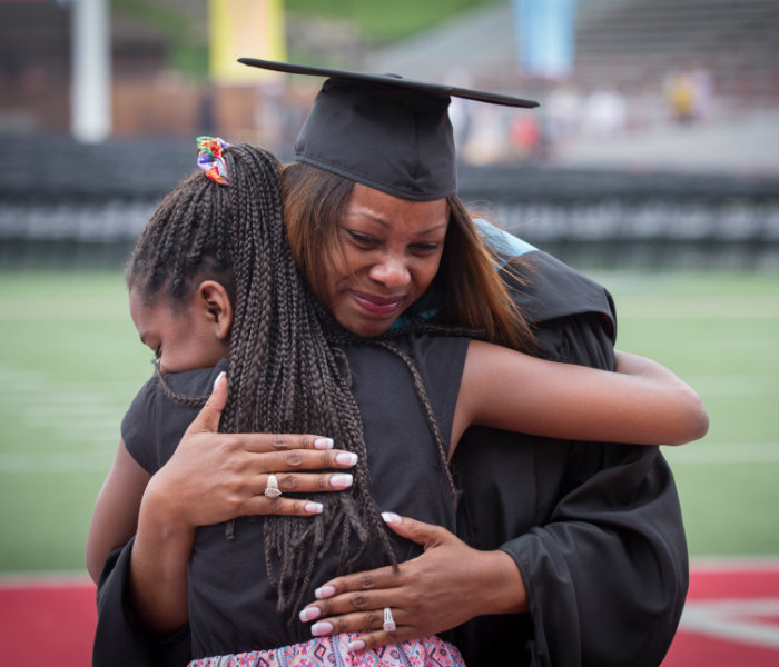 A recent graduate hugging her daughter at graduation