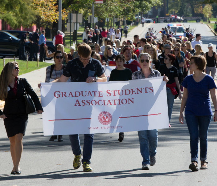 Group of students holding the Graduate Student Association banner
