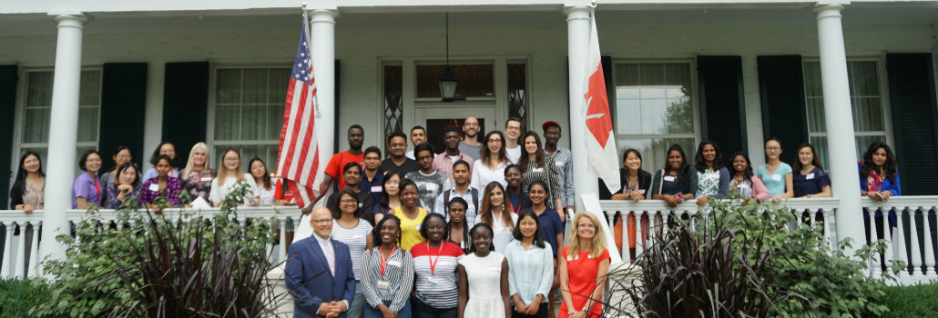 Group of new international graduate students in front of President Crawford's house with both Crawfords