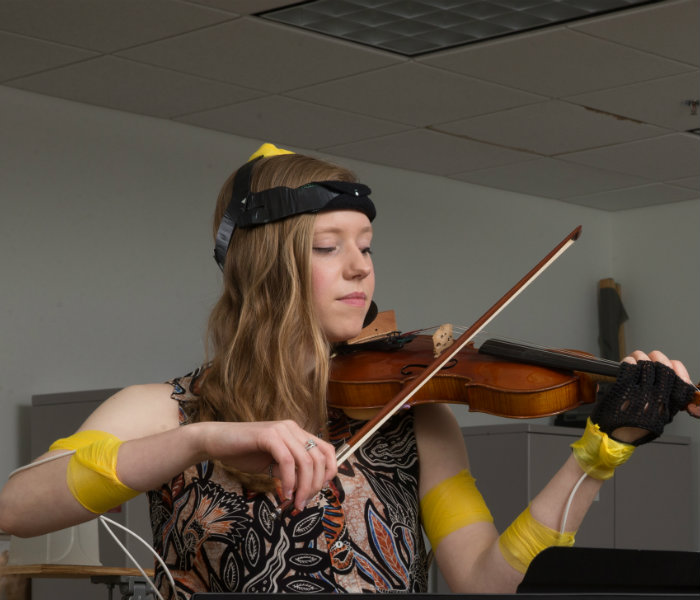 Female student playing violin while electrodes are on her arms