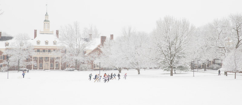 MacCracken hall in winter with students playing in snow