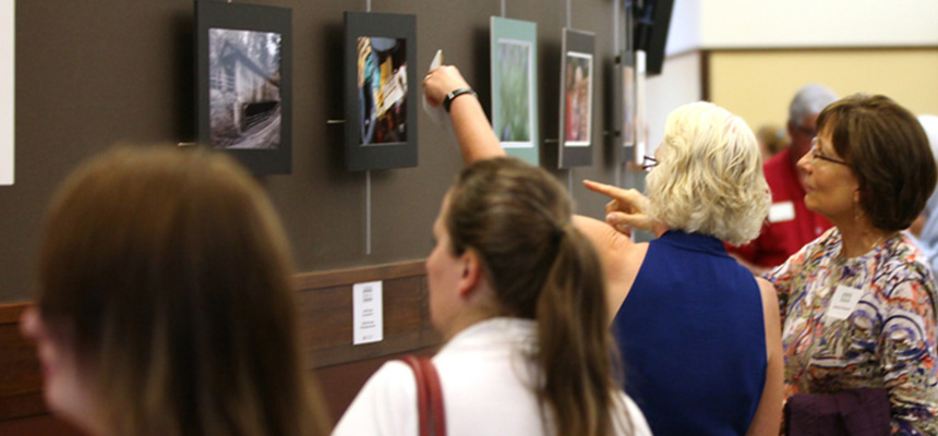 Visitors looking at artwork during an art show.