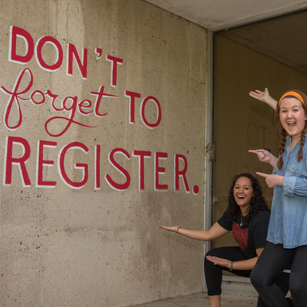 Don't Forget to Register painted on a wall with 4 students pointing to it. A academic advisor working with a student during a one-on-one appointment.
