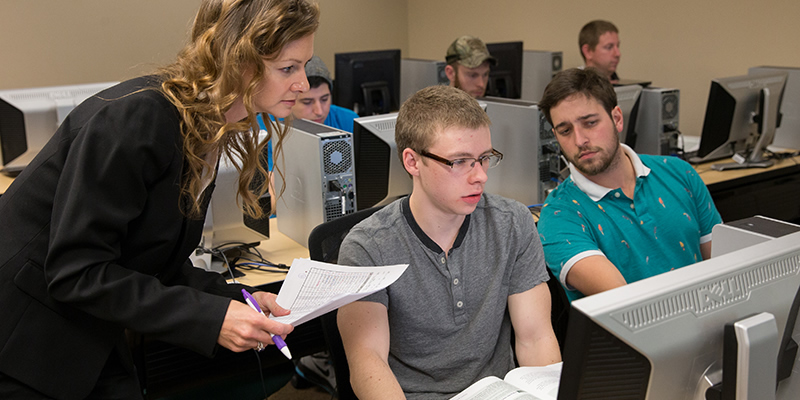 A professor talking to her students during a business software class.