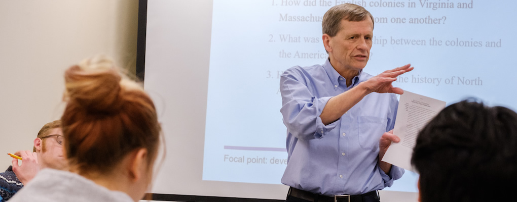 Rob Schorman standing in front of the classroom teaching with a piece of paper in his hand.