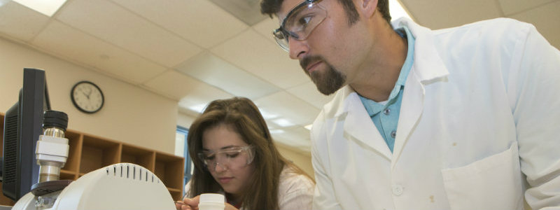 2 students working together on a lab project in white coats.