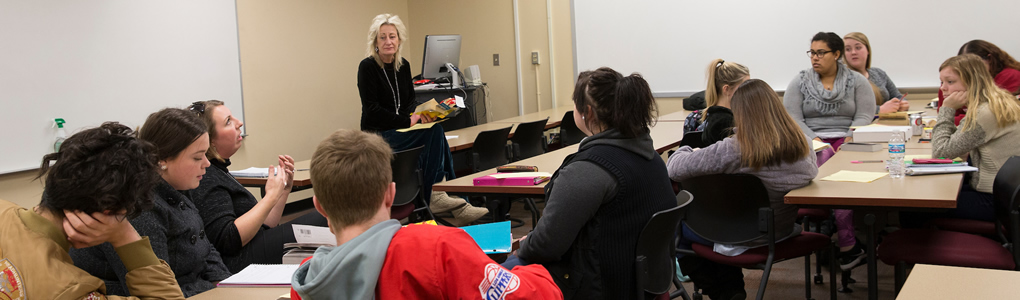 Professor Diana Royer standing in the front of the classroom teaching to her students.