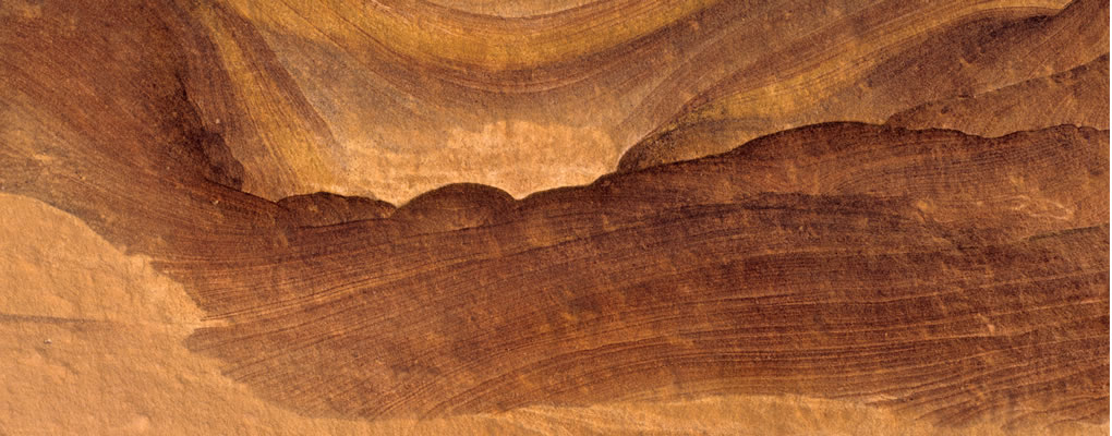 Close up of sandstone wall showing rich colors and multiple layers developed over millennia.