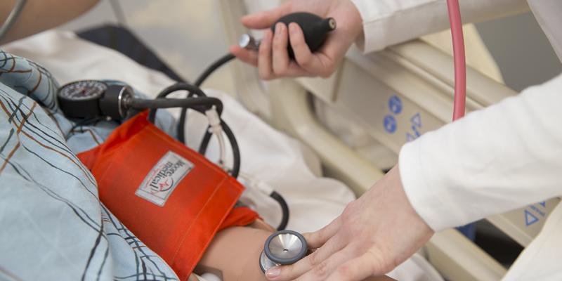 A student taking a patients blood pressure.