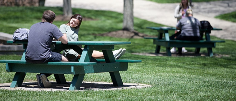 Students sitting at picnic tables in the quad of the Middletown campus.