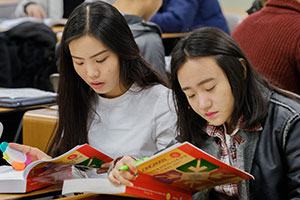 2 female students looking at their textbooks.