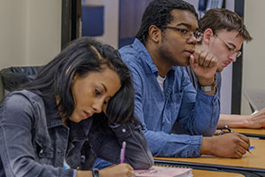 3 students taking notes during class time.