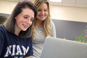 A female student looking at her laptop sitting down and another standing behind her looking.