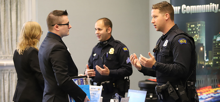 Male student speaking to male police officer at career fair
