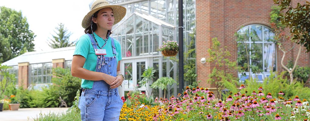 A student worker at the conservatory leading a tour of the formal gardens