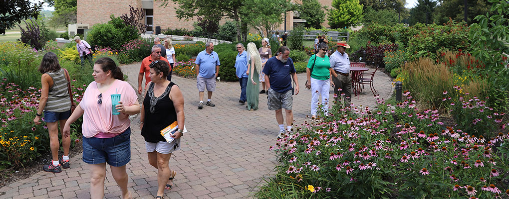 A group of people walking through the formal gardens.