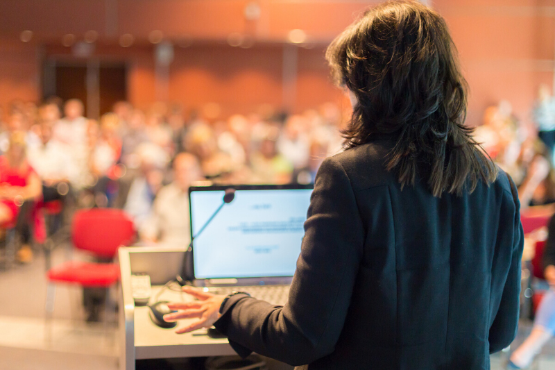 woman standing at a podium in a lecture hall